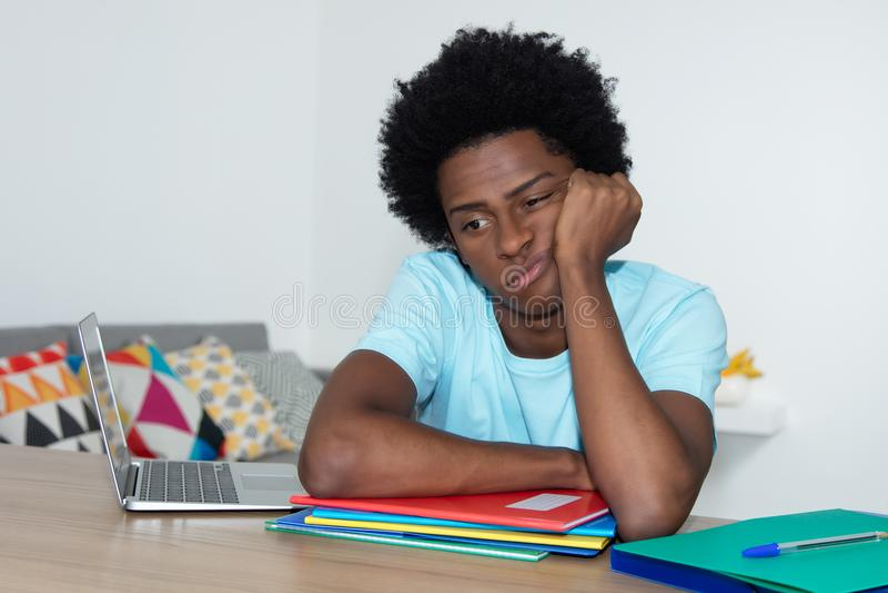 Unmotivated άνδρας σπουδαστής αφροαμερικάνων στο γραφείο στοκ εικόνες