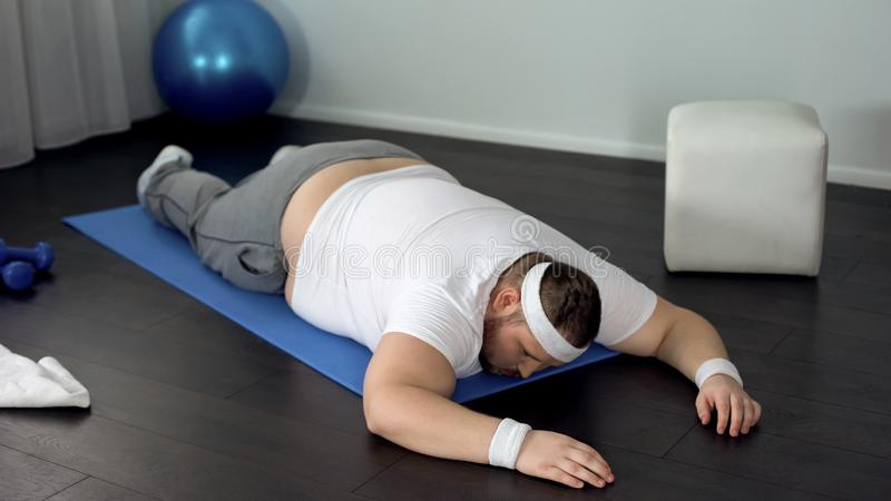 Unmotivated man lying on mat, giving up during exhausted muscles training royalty free stock photography