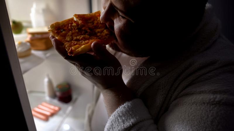 Unmotivated obese bachelor eating pizza near fridge at night, diet failure stock images