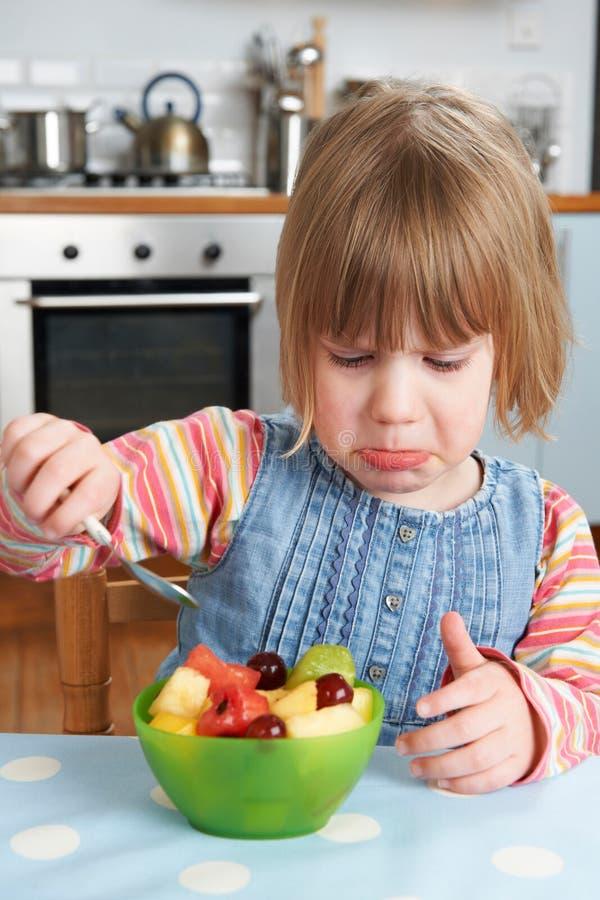 Unnötig geschäftiges Kind, das köstlichen Obstsalat-Pudding zurückweist lizenzfreies stockbild