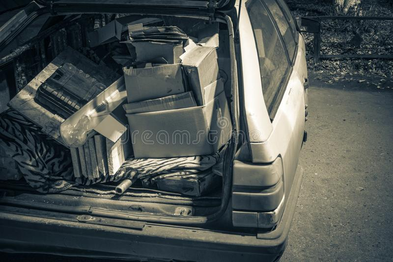 Unnecessary garbage carried in the trunk of an old car. Unnecessary garbage carried in the trunk of an old ca royalty free stock photo