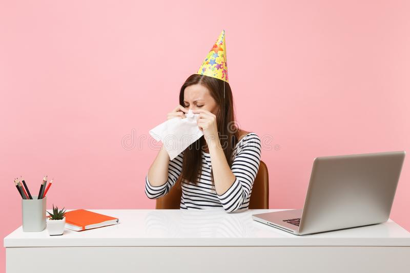 Unnerved woman in party hat crying wiping tears with tissue because celebrating birthday alone at office at white desk royalty free stock photos