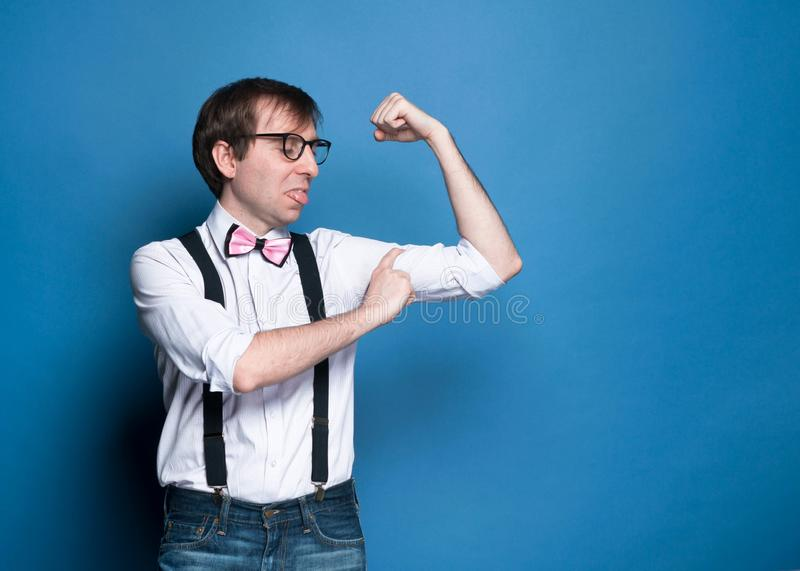Unny disappointed thin man measuring biceps with finger stock photo