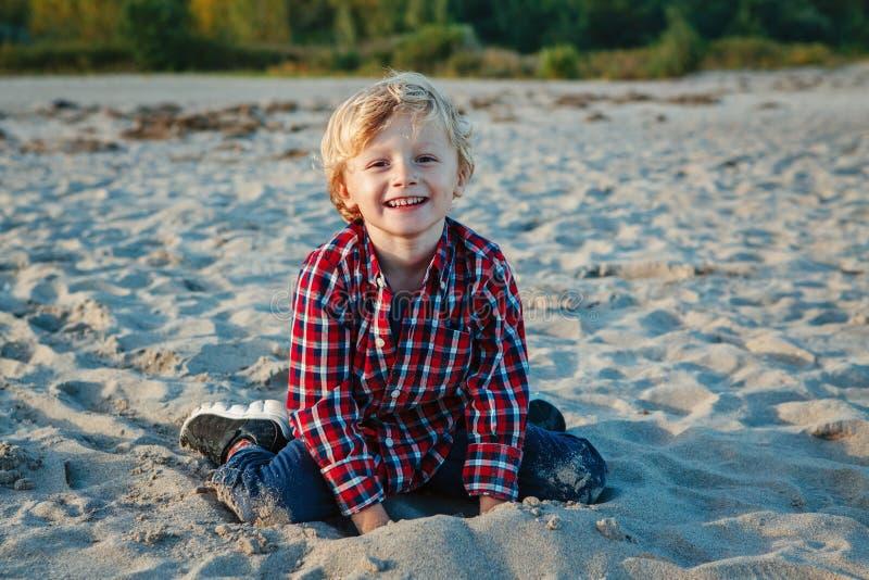 unny lächelnder lachender weißes kaukasisches Kinderkinderblonder Junge, sitzendes Spielen mit Sand auf Strand bei Sonnenuntergan stockfoto