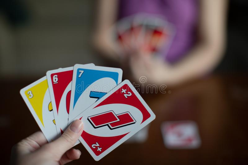 Playing american card game Uno, holding game cards in female hand. stock photos
