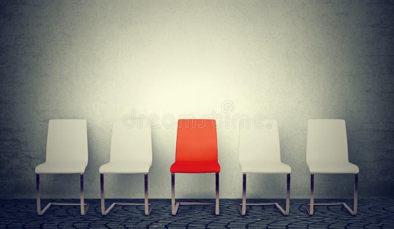 Uno che si apre per il concetto di lavoro Fila delle sedie bianche e di un rosso nel mezzo fotografia stock