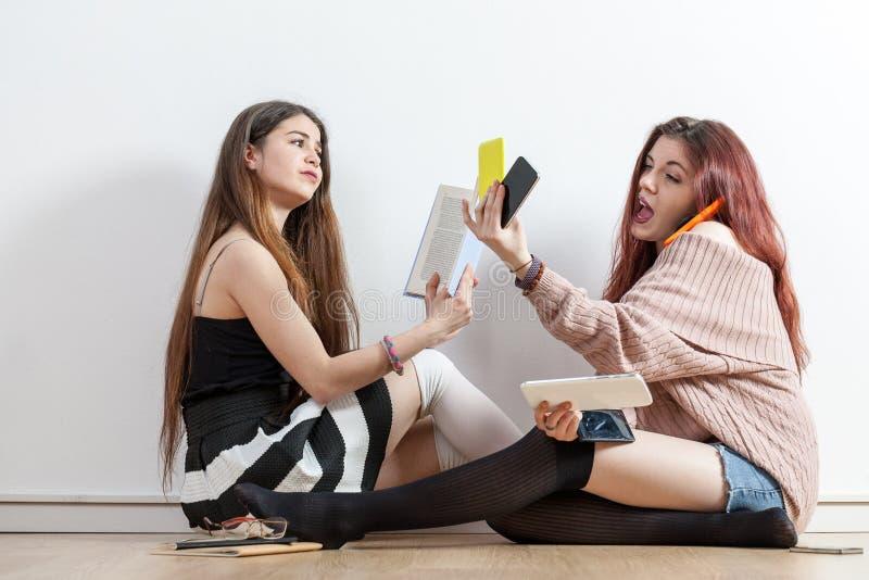 Uno con un libro uno con il cellulare fotografie stock