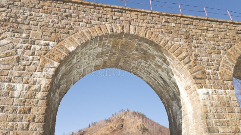 Uno de los arcos hermosos viejos en el ferrocarril de Circum-Baikal de las orillas del lago Baikal en la primavera fotografía de archivo