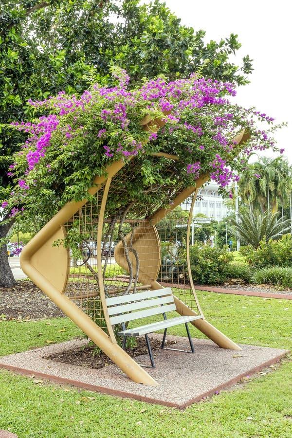 Uno de los bancos buganvilla-cubiertos hermosos del parque bicentenario de Darwin, Australia imagen de archivo