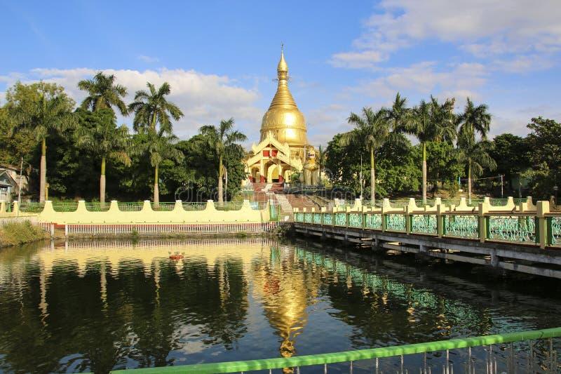Uno dei molti stupas dorati contro il cielo blu e lo stagno con fotografia stock
