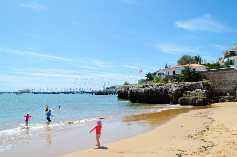 Uno della spiaggia di Cascais a Lisbona, con i bambini che giocano immagini stock
