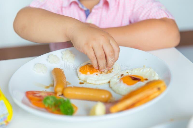 Uno mismo gordo del niño del muchacho que come la comida sana del huevo frito de la comida de la mañana imagen de archivo libre de regalías