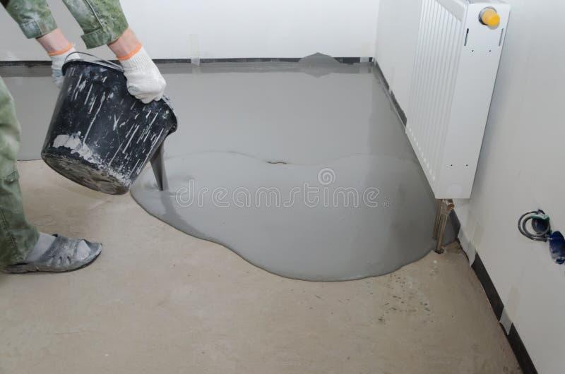 Uno mismo-nivelación del epóxido Nivelación con una mezcla de pisos del cemento fotos de archivo libres de regalías