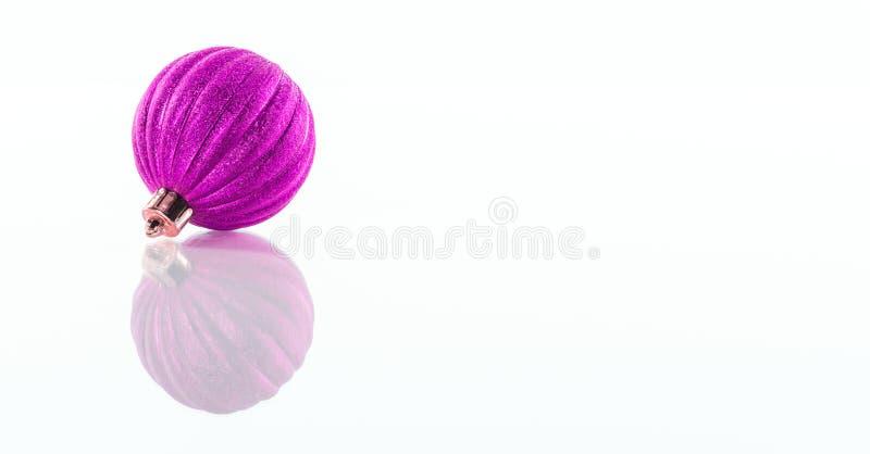 Uno púrpura, bola rosada de la Navidad aislada en el fondo reflexivo blanco del plexiglás fotos de archivo