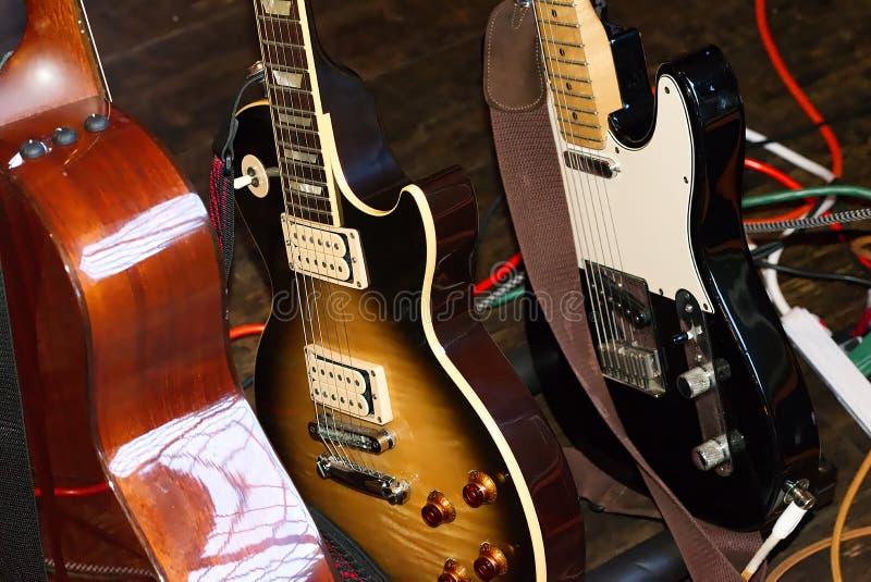 Uno scaffale con tre chitarre in scena fotografia stock