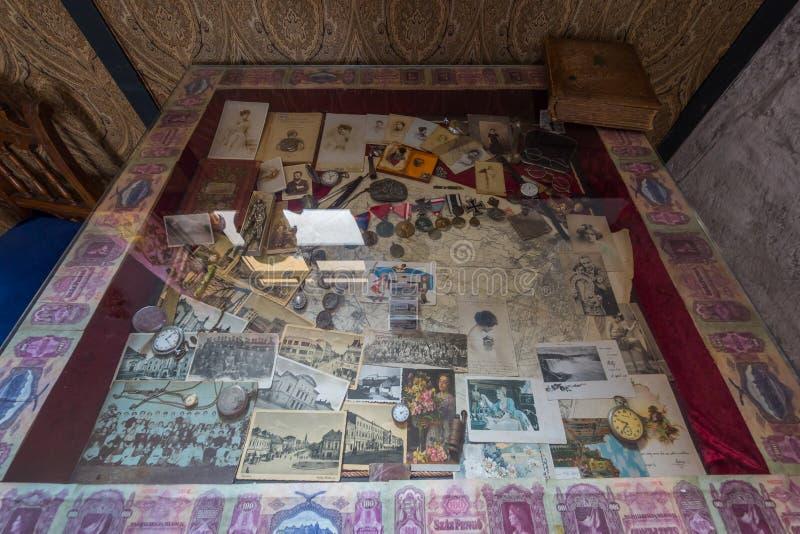 Uno scaffale di vetro con gli orologi, le fotografie, le monete ed i premi antichi Su è lo stesso vecchio libro immagini stock