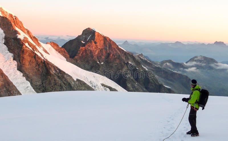Uno scalatore di montagna maschio sta su un alto ghiacciaio alpino all'alba ed ammira il ouf fantastico di vista il paesaggio cir fotografia stock libera da diritti
