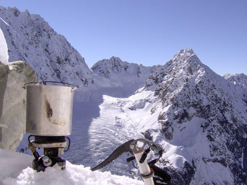 Uno scalatore di montagna prende una rottura all'alimento del cuoco nella neve fotografia stock