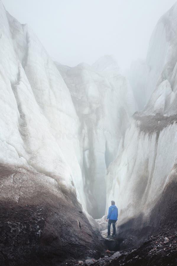 Uno scalatore libero con i supporti dell'ascia di ghiaccio al piede di grande ghiacciaio accanto ad una crepa epica nella nebbia  immagini stock