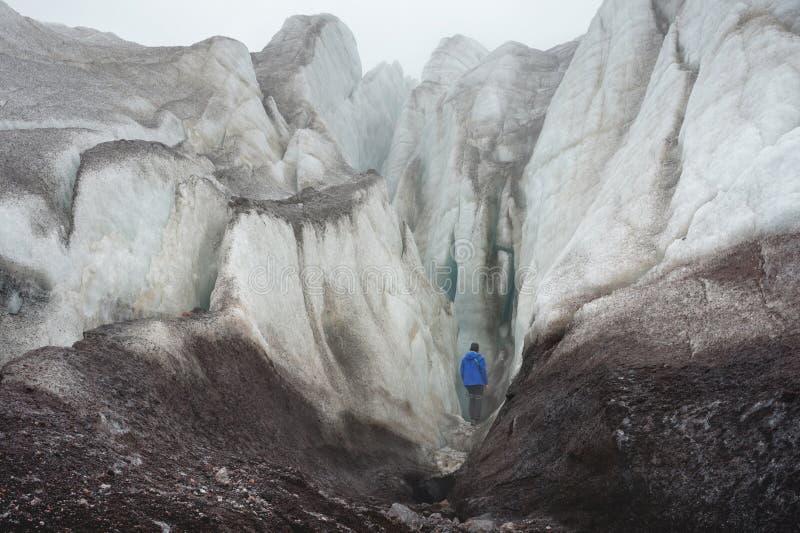 Uno scalatore libero con un'ascia di ghiaccio sta al piede di grande ghiacciaio accanto alla crepa epica in nebbia nelle montagne fotografie stock