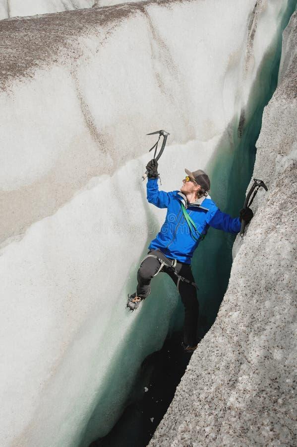 Uno scalatore libero senza assicurazione con due piccozze da ghiaccio aumenta da una crepa nel ghiacciaio Scalata libera senza co immagini stock