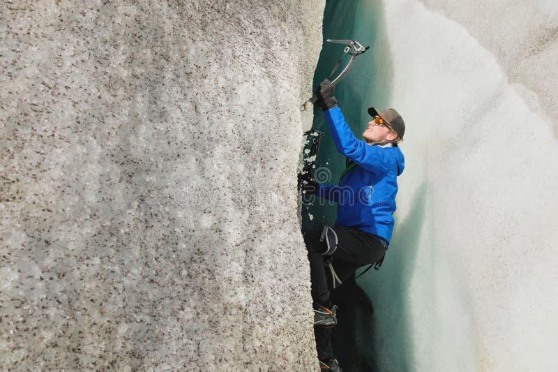 Uno scalatore libero senza assicurazione con due piccozze da ghiaccio aumenta da una crepa nel ghiacciaio Scalata libera senza co fotografie stock libere da diritti
