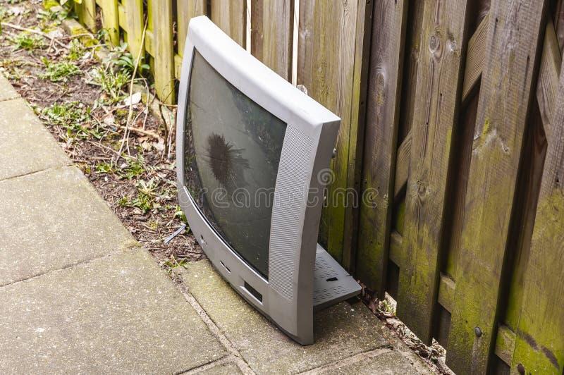 Uno schermo rotto della TV che sta sulla terra fotografie stock