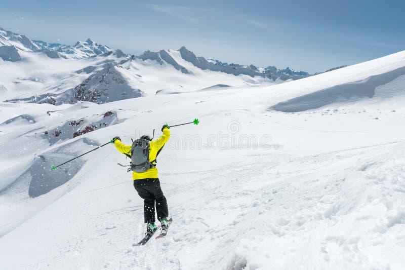 Uno sciatore in articolo sportivo pieno salta nell'abisso dalla cima del ghiacciaio contro lo sfondo del cielo blu immagini stock