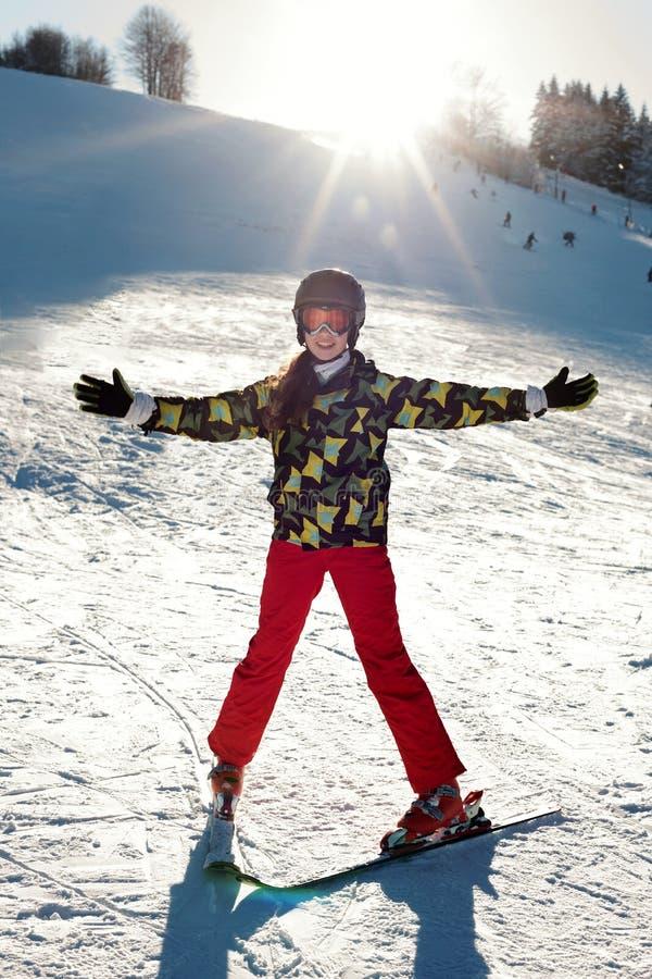 Uno sciatore della ragazza in pantaloni rossi ed in un rivestimento verde sugli sci che la allungano fuori armi soddisfatte del ` fotografia stock libera da diritti