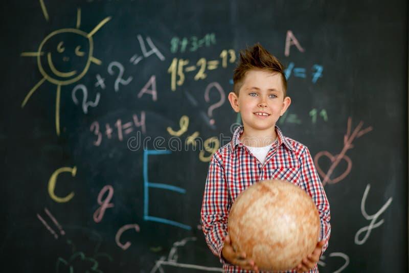 Uno scolaro che tiene un globo rotondo nelle mani di una lavagna dipinta con una lavagna immagine stock