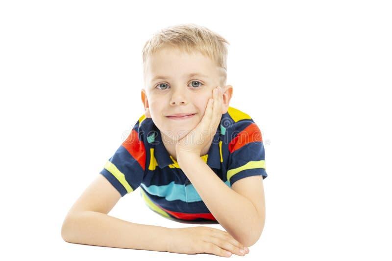 Uno scolaro in un maglione a strisce luminoso sta trovandosi sul pavimento e sul sorridere Isolato sopra fondo bianco immagine stock libera da diritti