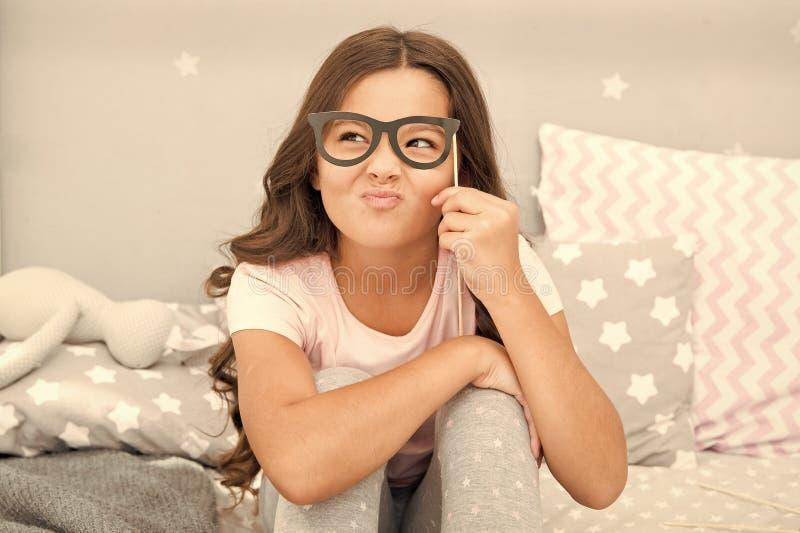 Uno sguardo intellettuale Piccola ragazza felice Piccoli vetri di falsificazione della tenuta della ragazza sul fronte Infanzia f immagini stock libere da diritti