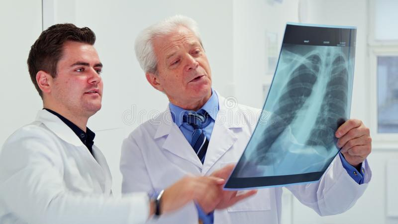 Uno sguardo maschio di due medici ai raggi x immagini stock libere da diritti