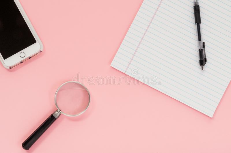Uno Smart Phone, un blocco, una penna e una lente d'ingrandimento su una s rosa fotografia stock