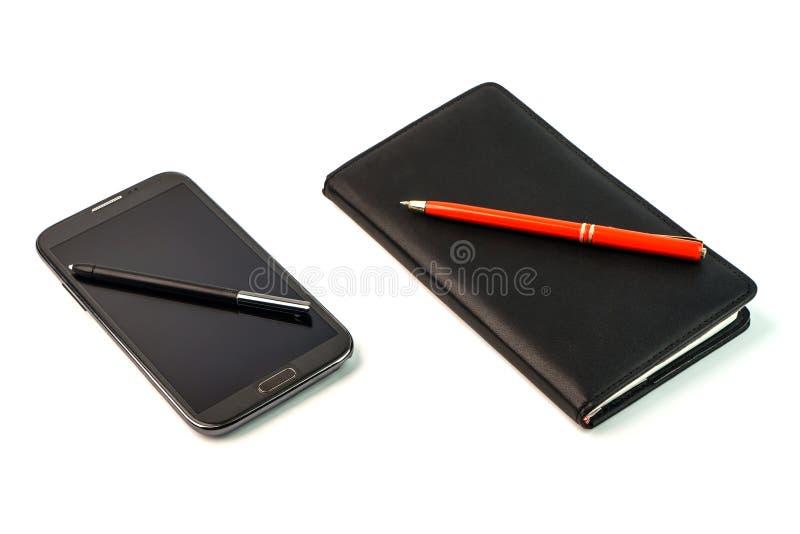 Uno smartphone con una penna dello stilo e un taccuino nero con la penna rossa fotografia stock libera da diritti