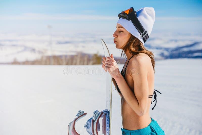Uno snowboard baciante della giovane donna immagini stock libere da diritti