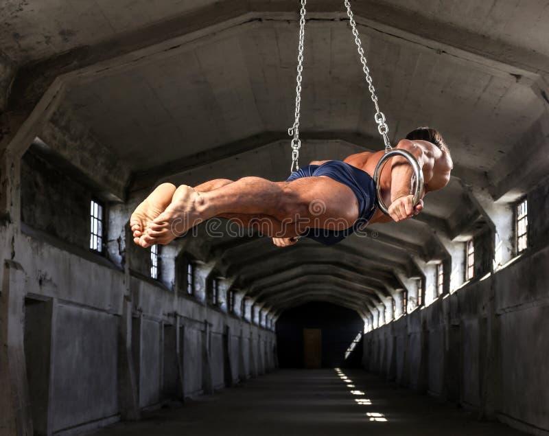 Uno sportivo professionista con treni i bei di un corpo muscolare sugli anelli relativi alla ginnastica in fabbricato industriale fotografia stock libera da diritti
