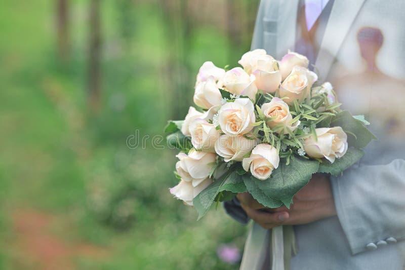 Uno sposo che tiene per mano un bouquet con scatto scattato prima del matrimonio immagine stock