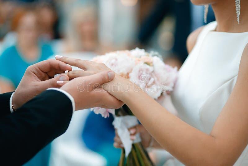 Uno sposo mette una fede nuziale sul dito del ` s della sposa fotografie stock libere da diritti