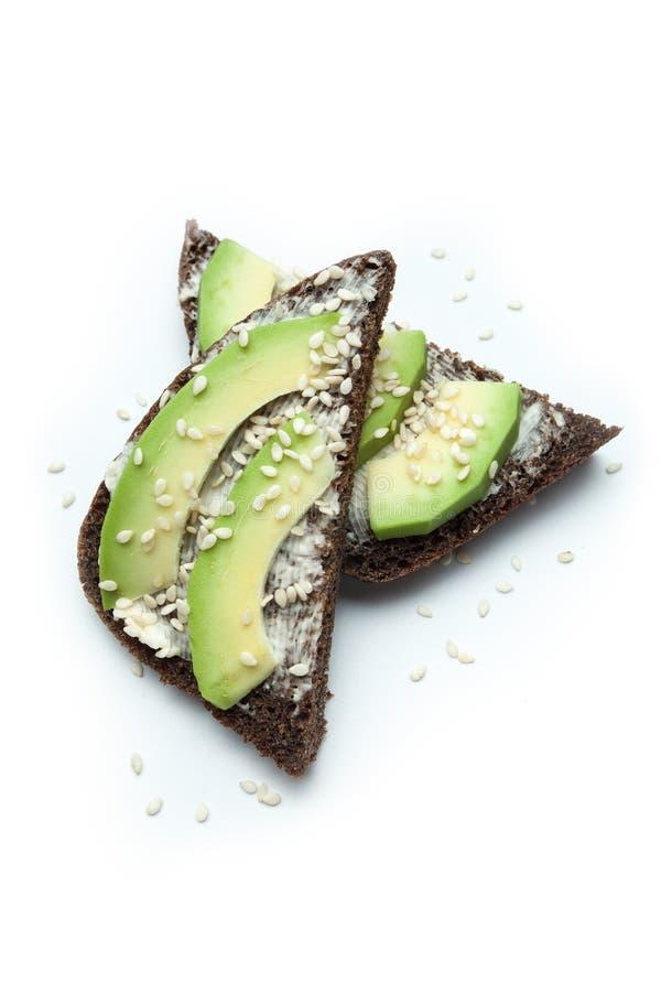 Uno spuntino dietetico semplice dalle fette di avocado, di formaggio fuso e di pane nero spruzzati con i semi di sesamo Isolato s fotografia stock libera da diritti