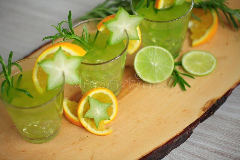 Uno standink verde di tre cocktail su legno, decorato con l'arancia, la carambola, la calce ed i rosmarini Ready per party fotografie stock