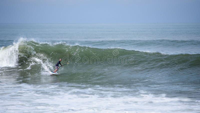 Uno stare sul pensionante della pagaia che pratica il surfing un'onda fotografie stock libere da diritti