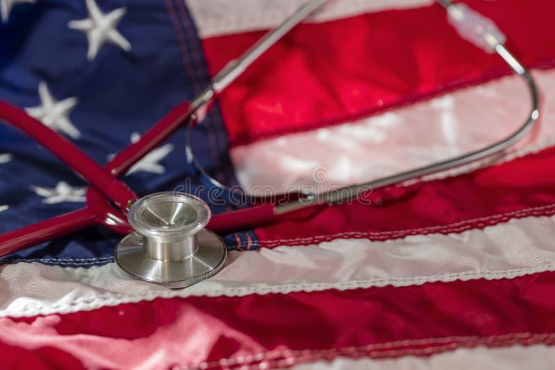 Uno stetoscopio medico su una bandiera americana che rappresenta Healthcar immagine stock libera da diritti