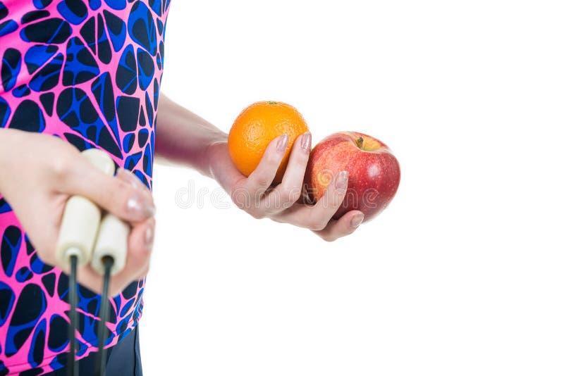 Uno stile di vita sano e una nutrizione adeguata Corda, mela ed arancia nelle mani di una ragazza, isolate su fondo bianco Horiz immagine stock libera da diritti