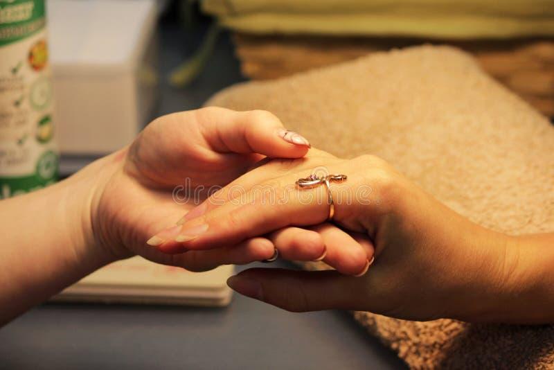 Uno studente ai corsi di formazione valuta la mano di un cliente di signora prima della preparazione per un manicure fotografia stock libera da diritti