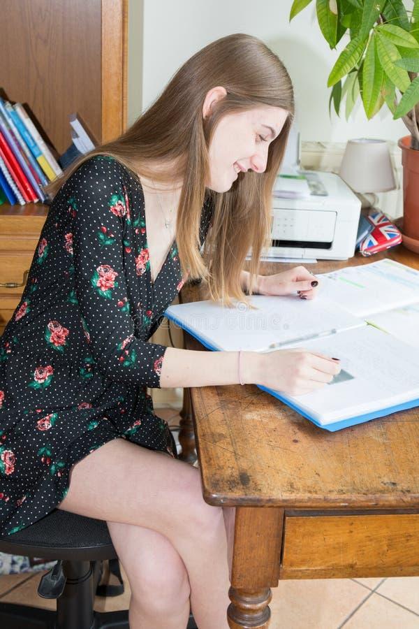 uno studente della donna in carriera della scuola a casa che lavora scrittura nella nota dell'istituto universitario fotografie stock