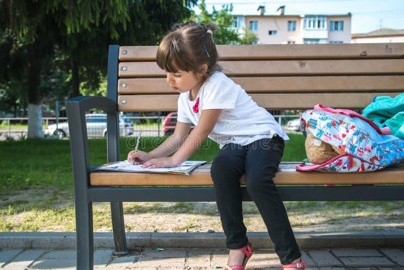 Uno studente della scuola elementare con uno zaino sta sedendosi su un banco e scrive qualcosa fotografie stock