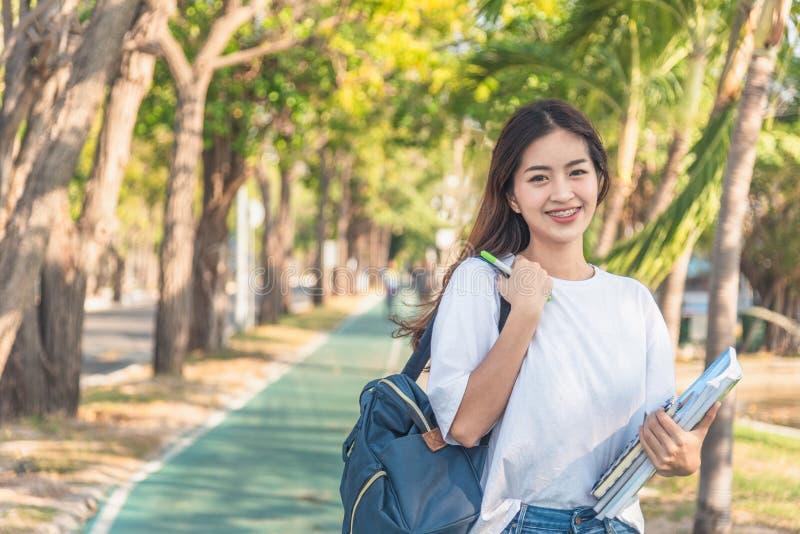 Uno studente di college femminile che legge un libro mentre trovandosi sul parco fotografia stock libera da diritti