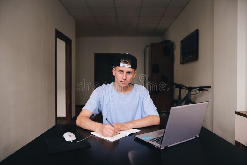 Uno studente fa un lavoro di compito mentre si siede nella sua casa Gli anni dell'adolescenza studiano a casa Uno sguardo alla ma immagine stock