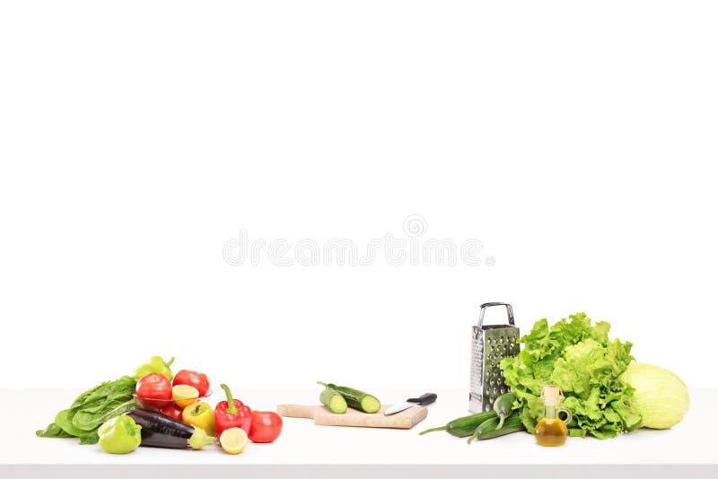 Uno studio ha sparato di una tavola in pieno dei ingridients per la preparazione dell'insalata fotografia stock libera da diritti